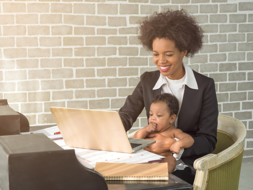 Young mother working from holding her baby